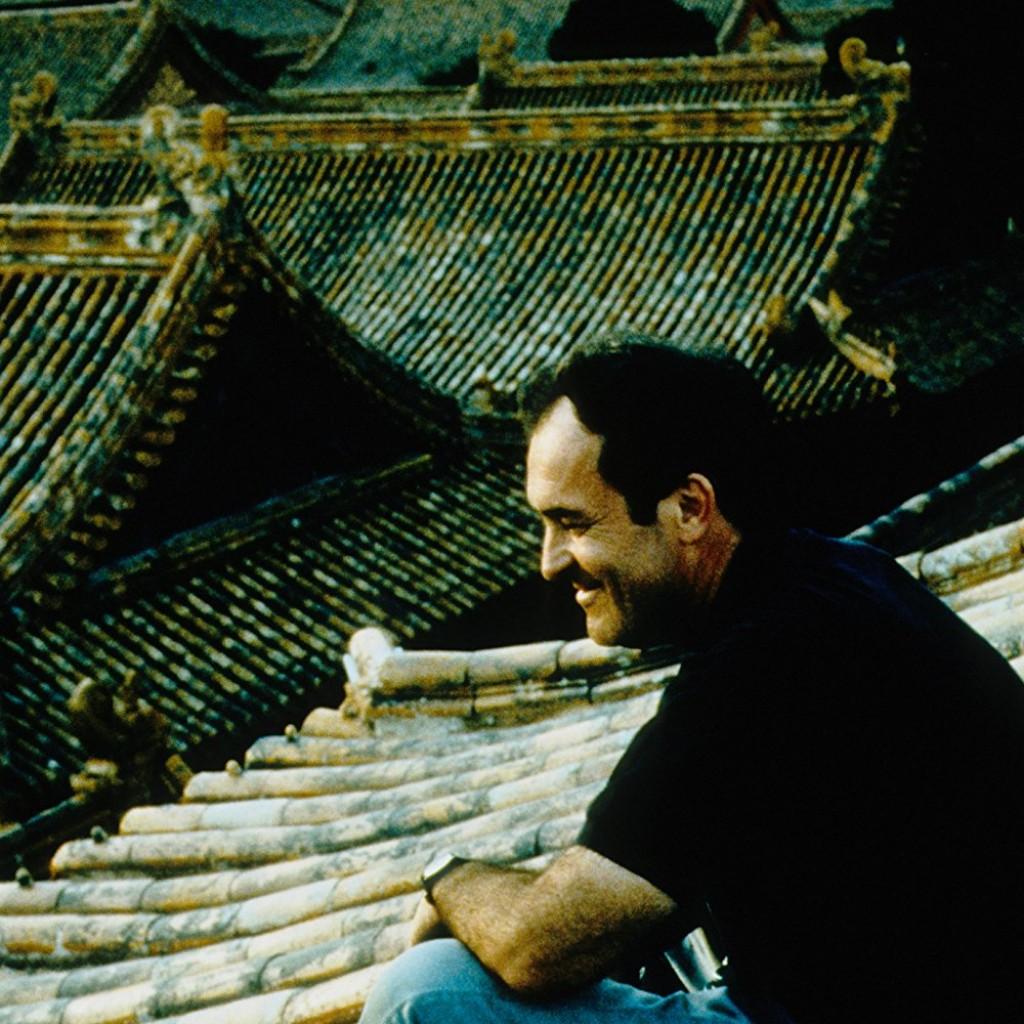 """Bernardo Bertolucci, fotografato sui caratteristici tetti della Città Proibita a Pechino, durante le riprese de """"L'Ultimo Imperatore"""""""